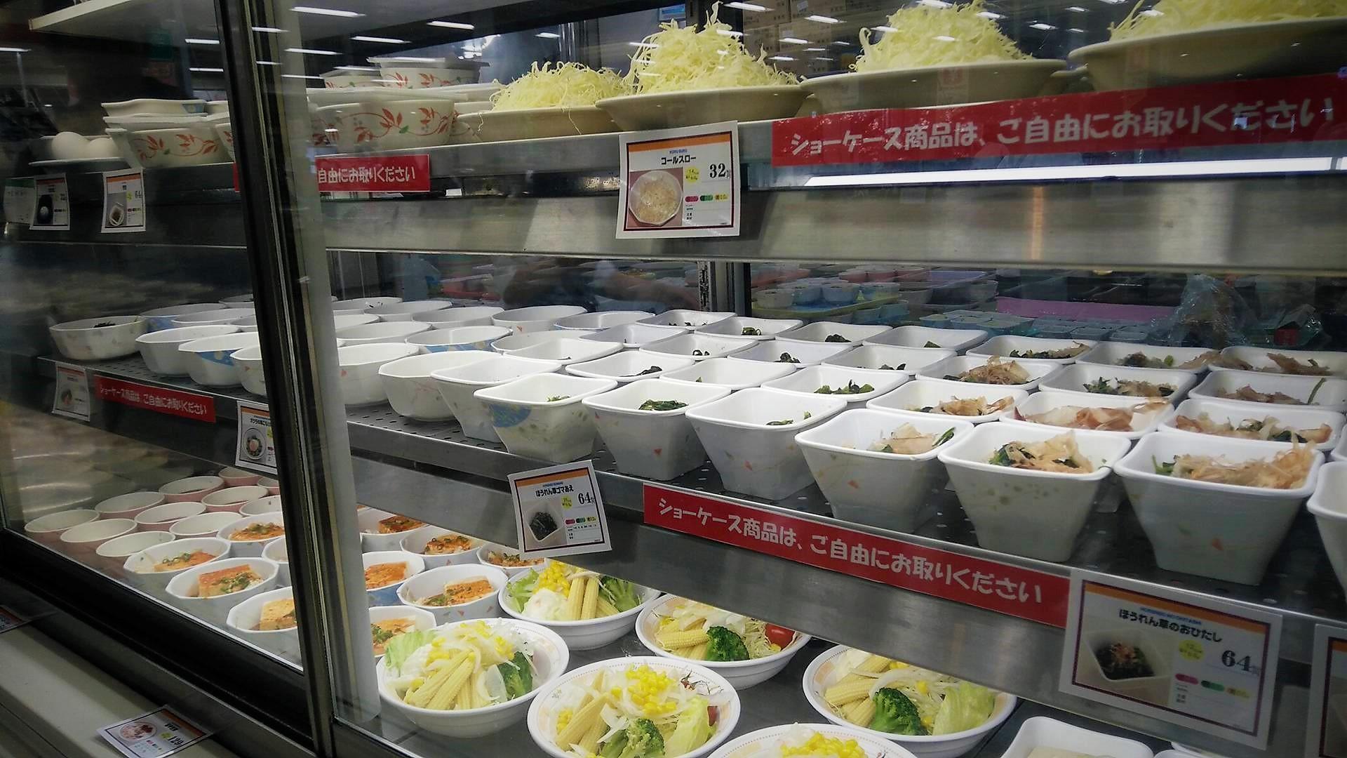 Toog met kleine bordjes groenten, tofu of vlees. Wat verder staat de vis en tonkatsu (schnitzels).